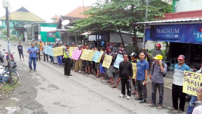 Warga Dukuhsari Jabon membentang kan poster turun jalan raya,menolak piminan kepala desa mantan narapidana (Memo /Agus HP)